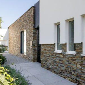 bruine steenstrips op de gevel van een moderne woning